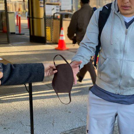 Gentleman handing another gentleman a mask