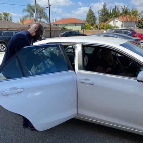 Man putting blue bag in car