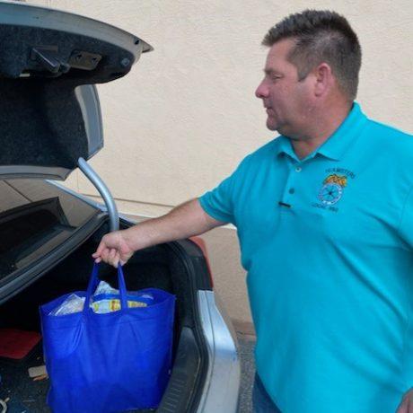 Man putting blue bag in trunk