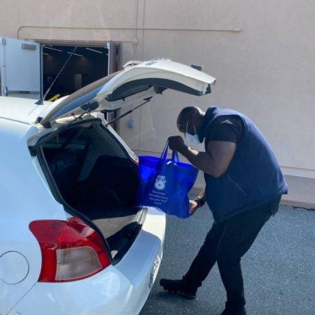 Man putting bag in trunk of car