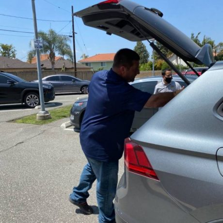 Man putting something in trunk of car